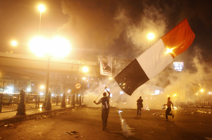 Supporters of Egyptian president Mohamed Mursi waving a national flag run from tear gas during clashes with riot police at the 6th October Bridge in the Ramsis square area in central Cairo July 15, 2013. (Reuters/Asmaa Waguih)