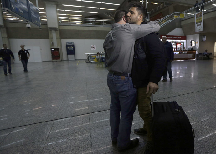 U.S. journalist Glenn Greenwald (front L) embraces his partner David Miranda upon his arrival at Rio de Janeiro's International Airport August 19, 2013. (Reuters/Ricardo Moraes)