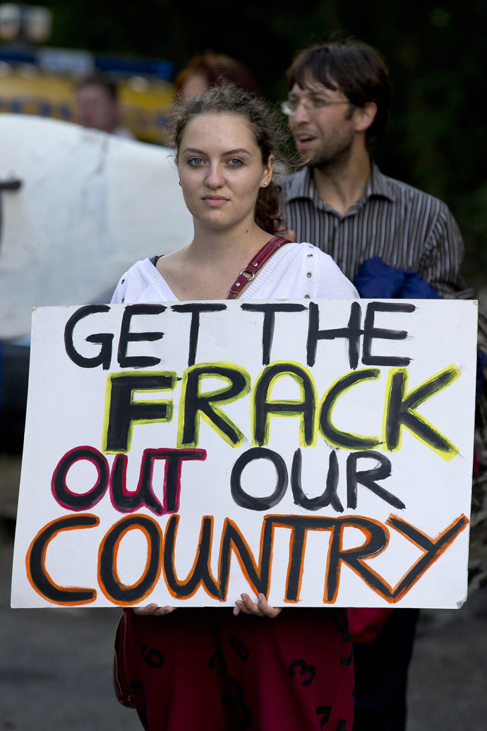 "An anti-fracking and climate protester holds a placard that reads ""Get the frack out our country"" as she joins a march towards the drill site operated by British energy firm Cuadrilla in Balcombe in southern England, on August 18, 2013. (AFP Photo/Justin Tallis)"