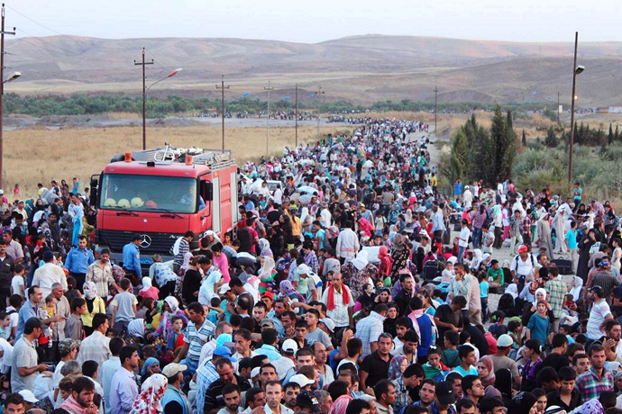 Thousands of Syrians streaming across a bridge over the Tigris River and entering the autonomous Kurdish region of northern Iraq (AFP Photo)