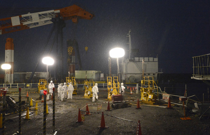 Workers wearing protective suits and masks operate a soil improvement work site of the shore barrier to stop radioactive water from leaking into the sea, near the No.1 and No.2 reactor buildings of the tsunami-crippled Fukushima Daiichi nuclear power plant in Fukushima, in this photo released by Kyodo July 22, 2013. (Reuters/Kyodo)