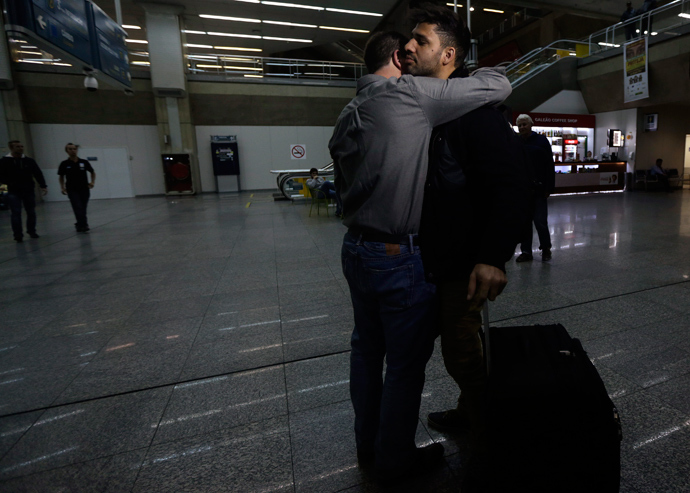 U.S. journalist Glenn Greenwald (front L) embraces his partner David Miranda upon his arrival at Rio de Janeiro's International Airport August 19, 2013 (Reuters / Ricardo Moraes)