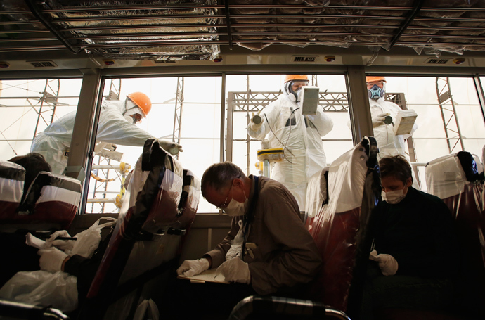 Workers carry out a radiation screening on a bus for a media tour at Tokyo Electric Power Co. (TEPCO)'s tsunami-crippled Fukushima Daiichi nuclear power plant (Reuters / Issei Kato)