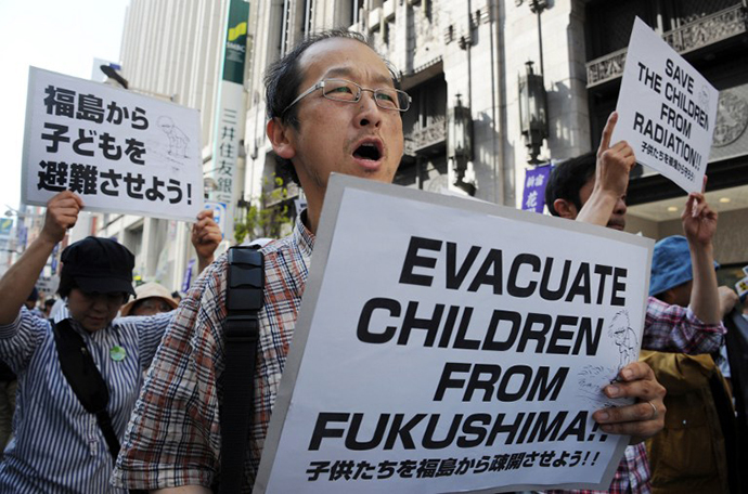 Protesters carry placards as they march in Tokyo's shopping district of Shinjuku on May 18, 2013 calling for the evacuation of children still living in the Fukushima prefecture area. (AFP Photo / Rie Ishii)