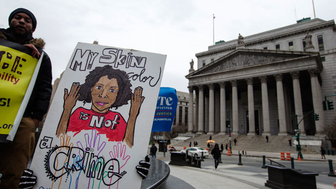 "Demonstrators hold signs protesting the New York Police Department's ""stop and frisk"" crime-fighting tactic outside of Manhattan Federal Court in New York, March 18, 2013.(Reuters / Lucas Jackson)"