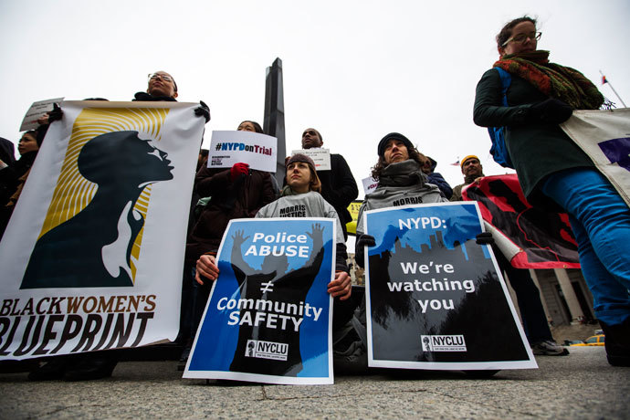 "Demonstrators hold signs protesting the New York Police Department's ""stop and frisk"" crime-fighting tactic outside of Manhattan Federal Court in New York, March 18, 2013. (Reuters / Lucas Jackson)"