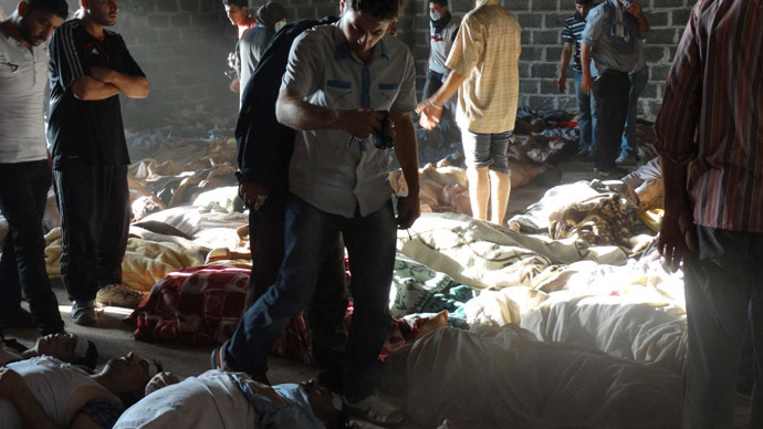 A handout image released by the Syrian opposition's Shaam News Network shows people inspecting bodies of children and adults laying on the ground as Syrian rebels claim they were killed in a toxic gas attack by pro-government forces in eastern Ghouta, on the outskirts of Damascus on August 21, 2013. (AFP Photo/Shaam News Network)