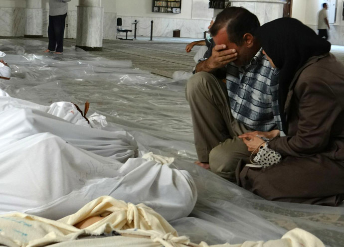 A handout image released by the Syrian opposition's Shaam News Network shows a Syrian couple mourning in front of bodies wrapped in shrouds ahead of funerals following what Syrian rebels claim to be a toxic gas attack by pro-government forces in eastern Ghouta, on the outskirts of Damascus on August 21, 2013. (AFP Photo/Shaam News Network)