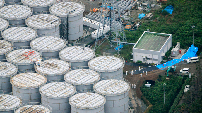 An aerial view shows workers wearing protective suits and masks working atop contaminated water storage tanks at Tokyo Electric Power Co. (TEPCO)'s tsunami-crippled Fukushima Daiichi nuclear power plant in Fukushima (Reuters / Kyodo)