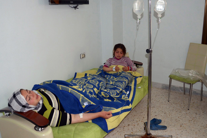 In this image made available by the Syrian News Agency (SANA) on March 19, 2013, a woman and a girl rest on a mattress at a hospital in the Khan al-Assal region in the northern Aleppo province, as Syria's government accused rebel forces of using chemical weapons for the first time (AFP Photo)