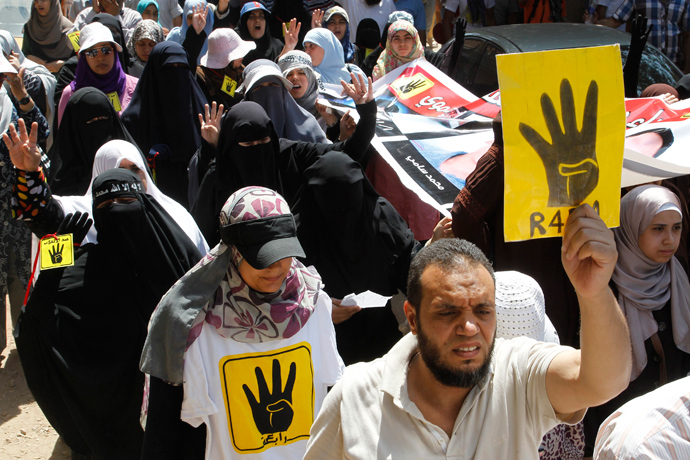 "Supporters of Muslim Brotherhood and ousted Egyptian President Mohamed Morsi hold up posters of the ""Rabaa"" gesture, in reference to the police clearing of Rabaa Adawiya protest camp on August 14, during a protest in Cairo August 23, 2013 (Reuters / Muhammad Hamed)"