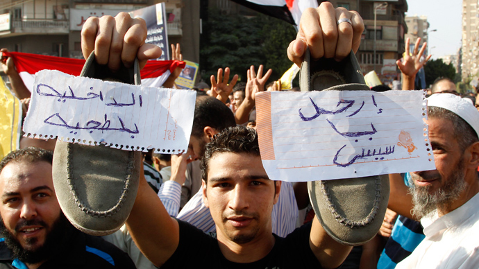 A supporter of Muslim Brotherhood and ousted Egyptian President Mohamed Mursi shows his shoes with notes written on them during a protest in Cairo August 23, 2013 (Reuters / Muhammad Hamed)
