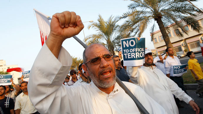 """An anti-government protester holding Bahraini flags and signs saying """"No To Official Terror"""" march during a rally organized by Bahrain's main opposition party Al Wefaq on Budaiya highway west of Manama August 23, 3013. (Reuters / Hamad I Mohammed)"""