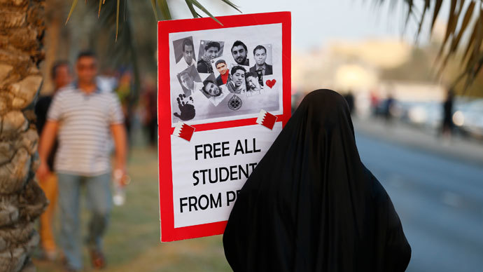 "An anti-government protester holds up a sign with photos of students detainees that read, ""Free All Students from Prison"" as she walks to the female area during a rally organized by Bahrain's main opposition party Al Wefaq on Budaiya highway west of Manama, August 23, 3013.(Reuters / Hamad I Mohammed)"