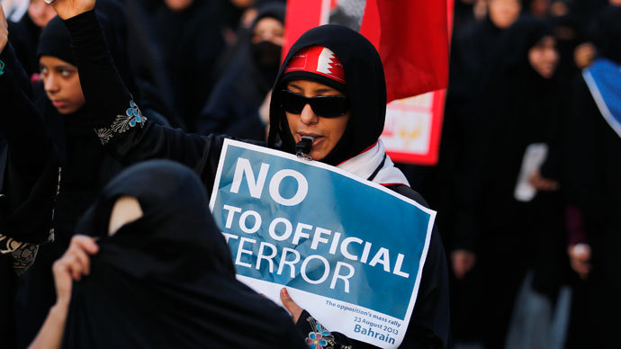 """Anti-government protesters holding Bahraini flags and signs saying """"No To Official Terror"""" march during a rally organized by Bahrain's main opposition party Al Wefaq on Budaiya highway west of Manama August 23, 3013. (Reuters / Hamad I Mohammed)"""