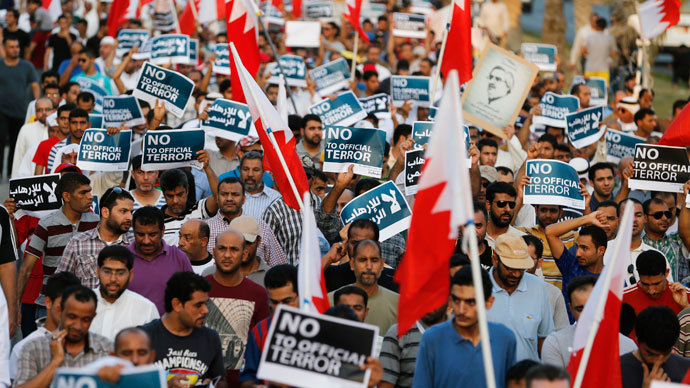 """Anti-government protesters holding Bahraini flags and signs saying """"No To Official Terror"""" march during a rally organized by Bahrain's main opposition party Al Wefaq on Budaiya highway west of Manama, August 23, 3013.(Reuters / Hamad I Mohammed)"""