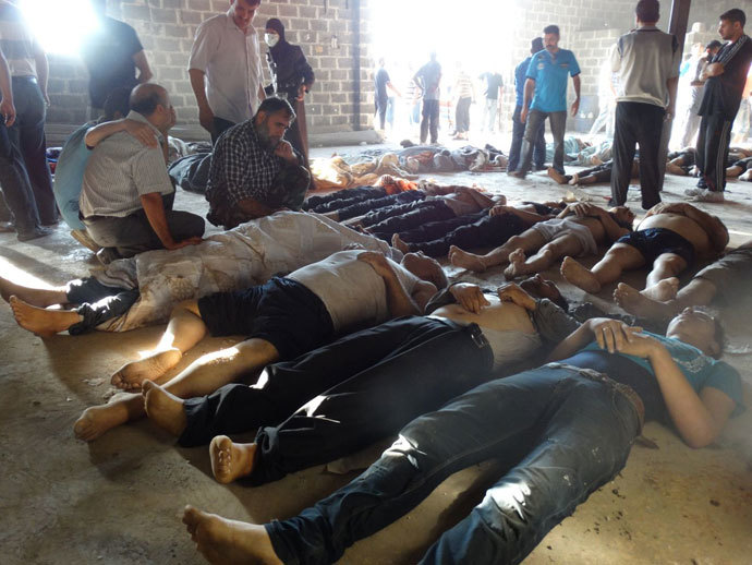 A handout image released by the Syrian opposition's Shaam News Network shows people inspecting bodies of children and adults laying on the ground as Syrian rebels claim they were killed in a toxic gas attack by pro-government forces in eastern Ghouta, on the outskirts of Damascus on August 21, 2013. (AFP Photo / Shaam News Network)