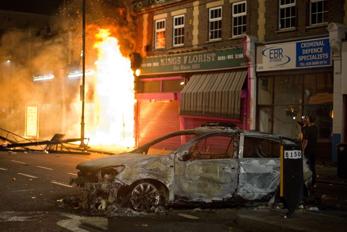 A shop burns as riot police try to contain a large group of people on a main road in Tottenham, north London on August 6, 2011 (AFP Photo / Leon Neal)