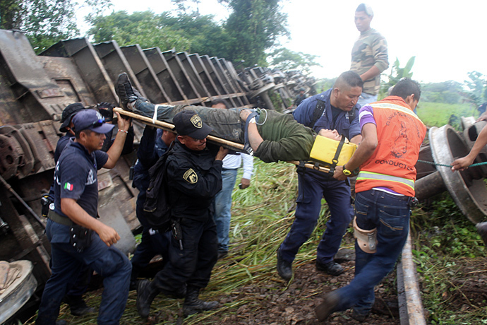 "Alleged immigrant being pulled from under the train known as ""The Beast"" which derailed near Huimanguillo, in Tabasco State, Mexico, on August 25, 2013 (AFP Photo / Tabasco Hoy)"