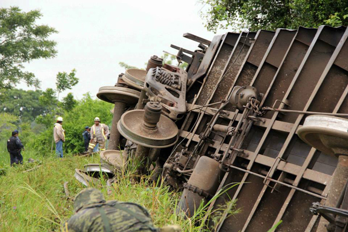 "Federal policemen, soldiers and rescuers working at the site where the train known as ""The Beast"" derailed, near Huimanguillo, in Tabasco State, Mexico, on August 25, 2013 (AFP Photo / Civil Protection Mexico)"
