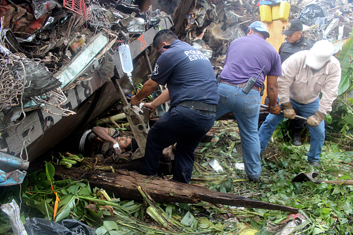 """Mexican state policemen helping trapped people after a train, known as """"The Beast"""", derailed near Huimanguillo, Tabasco State, Mexico, on August 25, 2013 (AFP Photo / Tabasco Hoy)"""