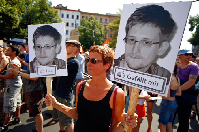 A protester carry two portraits of Edward Snowden during a demonstration against secret monitoring programmes PRISM, TEMPORA, INDECT and showing solidarity with whistleblowers Edward Snowden, Bradley Manning and others in Berlin July 27, 2013 (Reuters / Pawel Kopczynski)