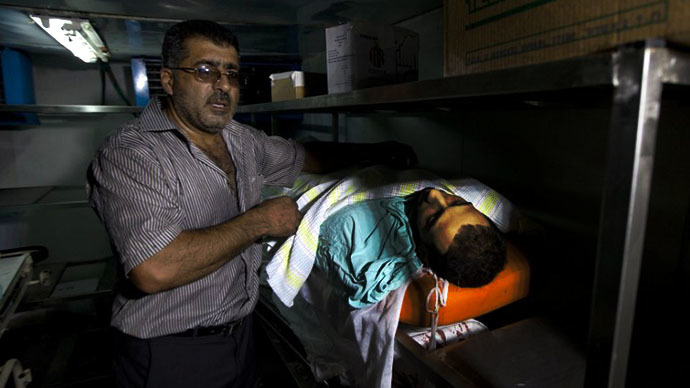 A man shows the body of a Palestinian man who was killed during clashes with Israeli security forces in Qalandia refugee camp, at a hospital in the West Bank city of Ramallah on August 26, 2013. (AFP Photo / Ahmad Gharabli)
