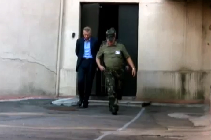 Vladislav Baumgertner handcuffed and led into a holding cell, as shown by Belorusian state TV chanel 'Novosti'. Taken from a video by ONT TV channel.