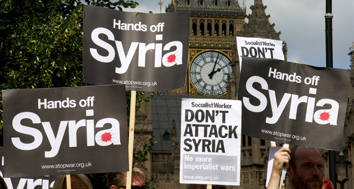Demonstrators hold up placards during a protest against potential British military involvement in Syria at a gathering outside the Houses of Parliament in central London on August 29, 2013. (AFP Photo / Andrew Cowie)