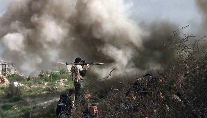An image grab taken from a video shows opposition fighter holding a rocket propelled grenade (RPG) as his fellow comrades take cover from an attack by regime forces during clashes over the strategic area of Khanasser, situated on the only road linking Aleppo to central Syria. (AFP Photo / Salah Al-Ashkar)