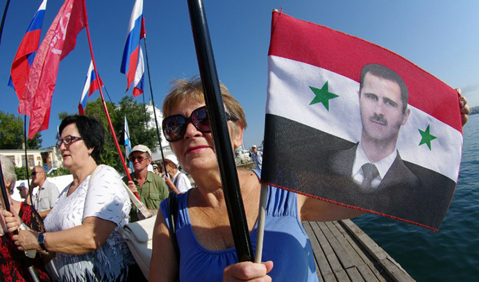 Ukrainian communists hold a Syrian flag bearing the picture of Syrian president Bashar al-Assad during a protest in his support and against the visit of the Standing NATO Mine Countermeasure Group SNMCMG2 to Sevastopol on August 29, 2013. (AFP Photo / Vasiliy Batanov)