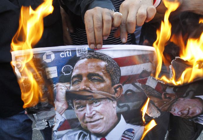 protester holds a poster burning on which is depicted former US president George W. Bush taking off a mask of current President Barack Obama during a demonstration of supporters of Syrian regime near the US embassy, east of Beirut against a possible US military strike on Syria on September 7, 2013. (AFP Photo)
