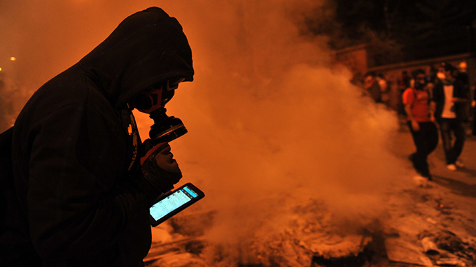 A protestor uses Facebook on mobile phone to give latestt news about the clashes near Taksim in Istanbul on June 3, 2013 during a demonstration against the demolition of the park. (AFP Photo / Ozan Kose)