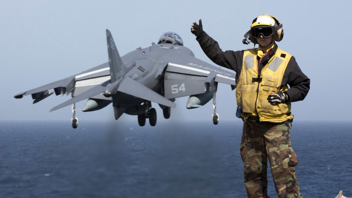A picture released by the US Navy shows Aviation Boatswain's Mate (Handling) 2nd Class Christiana Marszalek signaling as an AV-8B Harrier takes off from the amphibious assault ship USS Kearsarge (LHD 3) on March 29, 2013 in the Mediterranean Sea. (AFP Photo/US NAVY/Corbin Shea)