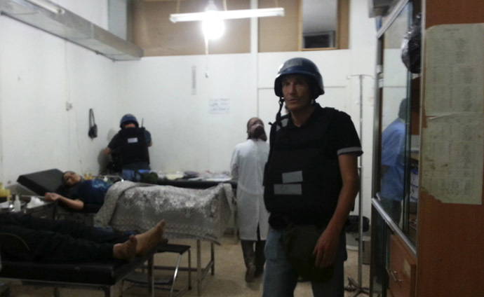 U.N. chemical weapons experts visit wounded people affected by an apparent gas attack, at a hospital in the southwestern Damascus suburb of Mouadamiya, August 26, 2013. (Reuters/Abo Alnour Alhaji)