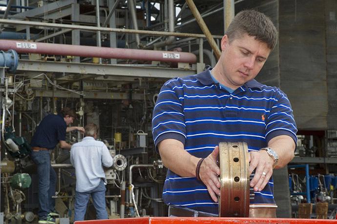 Propulsion systems engineer Greg Barnett prepares a rocket injector for a hot fire test at NASA's Marshall Space Flight Center. (NASA/MSFC/Emmett Given)