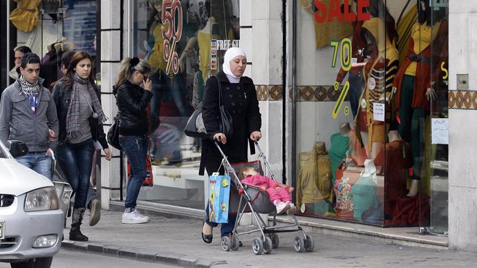 People walk past shop windows in the Syrian capital Damascus (AFP PHhoto / Louai Beshara)