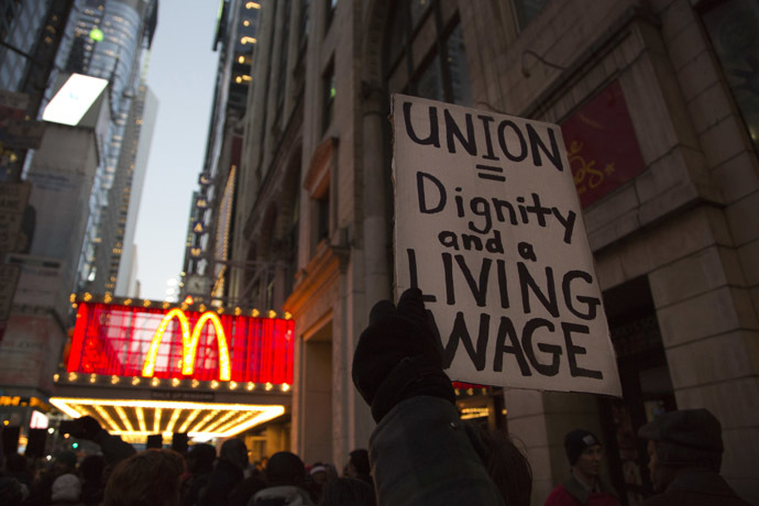 A protester holds up a sign at a demonstration outside McDonald's in Times Square in support of employees on strike at various fast-food chains in New York November 29, 2012. (Reuters/Andrew Kelly)