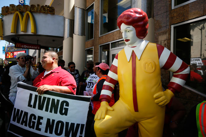 Striking McDonald's worker Bartolome Perez, 42, (L) protests outside McDonald's on Hollywood Boulevard as part of a nationwide strike by fast-food workers to call for wages of $15 an hour, in Los Angeles, California August 29, 2013.(Reuters / Lucy Nicholson)