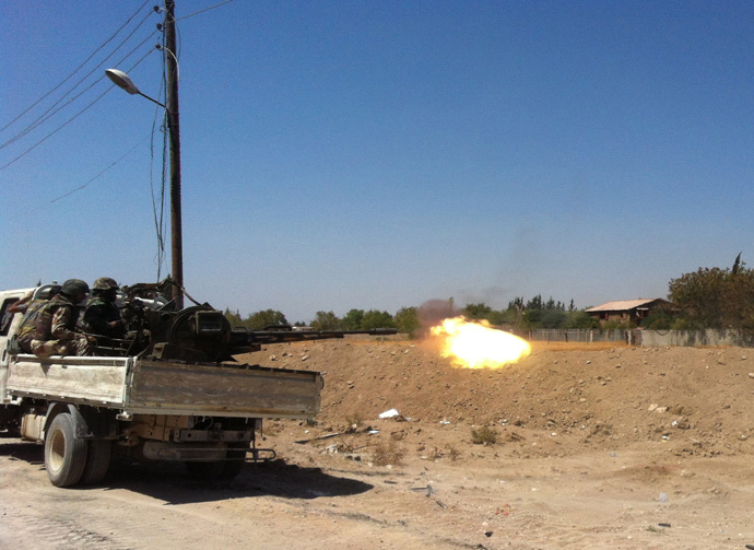 Syrian troops fire a heavy machine gun mounted on a pick-up truck in the Eastern Ghouta area on the northeastern outskirts of Damascus on August 30, 2013 (AFP Photo / Sam Skaine)