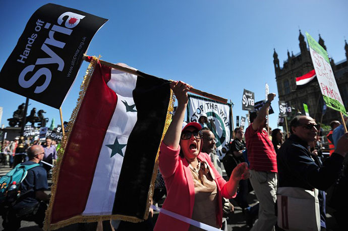 Protesters shout slogans and wave the Syrian flag as they demonstrate against military intervention in Syria in central London on August 31, 2013. (AFP Photo / Carl Court)