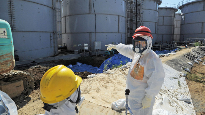 Japan's Economy, Trade and Industry Minister Toshimitsu Motegi (R), wearing a protective suit and a mask, inspects contaminated water tanks at the tsunami-crippled Fukushima Daiichi nuclear power plant in Fukushima prefecture August 26, 2013, in this photo released by Kyodo.  (Reuters/Kyodo)