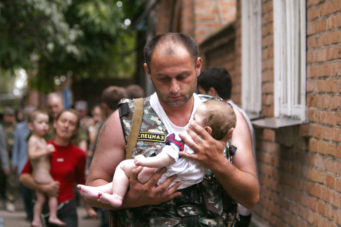 A Russian police officer carries a released baby from the school seized by heavily armed masked men and women in the town of Beslan (Reuters / Viktor Korotayev)