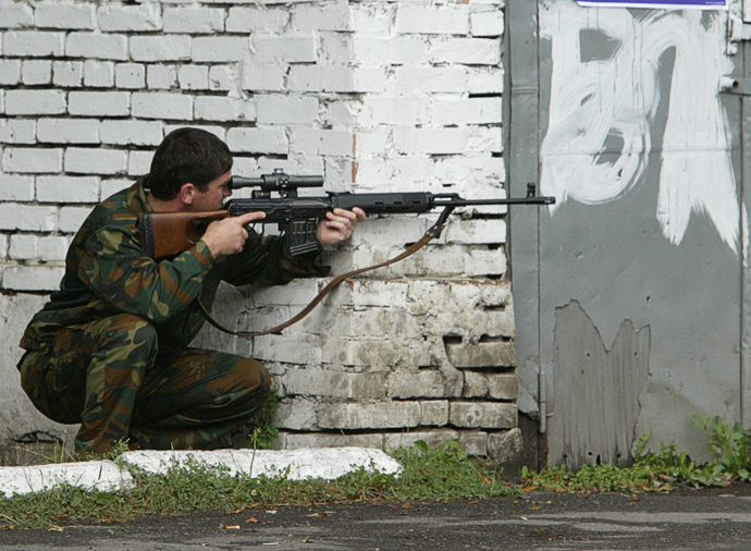 A Russian special police officer aims his rifle near the school seized by heavily armed masked men and women in the town of Beslan in the province of North Ossetia near Chechnya, September 2, 2004 (Reuters / Viktor Korotayev)
