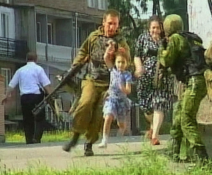 A television grab shows a soldier helping a girl away from the scene at a school in the town of Beslan in the province of North Ossetia (Reuters / Reuters TV)