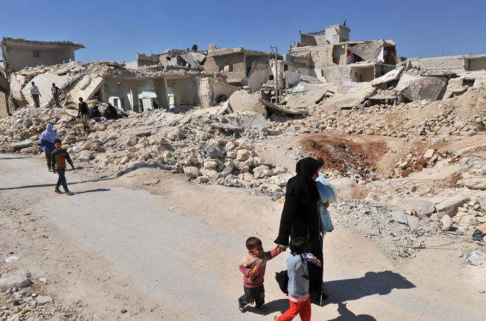 Syrians walk past destroyed buildings in the northern city of Aleppo (AFP Photo)