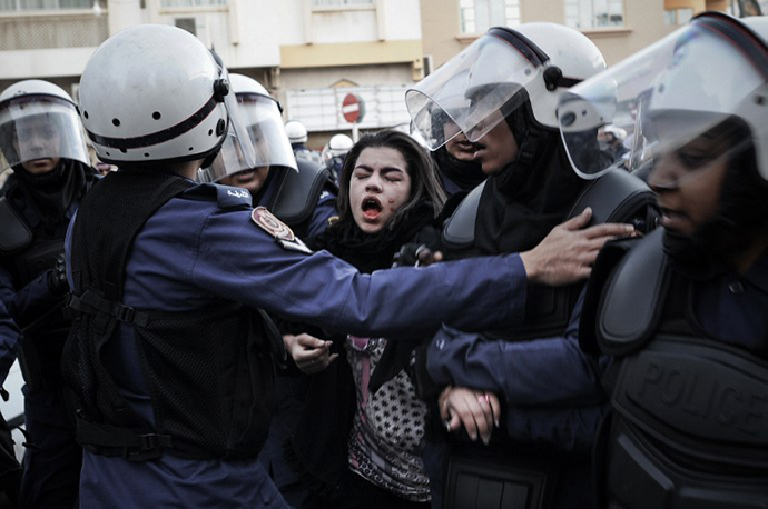 A protestor cries after being pepper sprayed as she is arrested by riot policemen during a demonstration called for by the February 14 Youth Coalition, an Internet group that regularly calls for protests in the Shiite-majority kingdom on January 18, 2013 in the capital Manama. (AFP Photo / Mohammed Al-Shaikh)