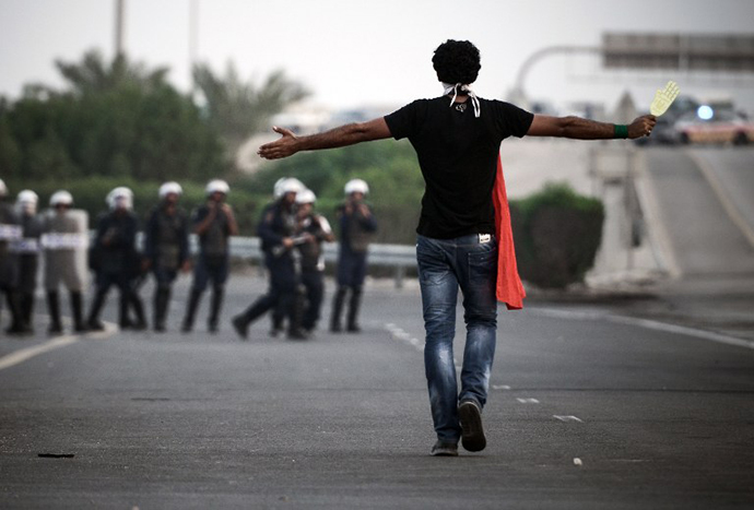 A Bahraini protester stands facing riot police during clashes following the funeral of Sadeq Sabt, in the village of North Sehla, west of Manama, on September 1, 2013. (AFP Photo / Mohammed Al-Shaikh)