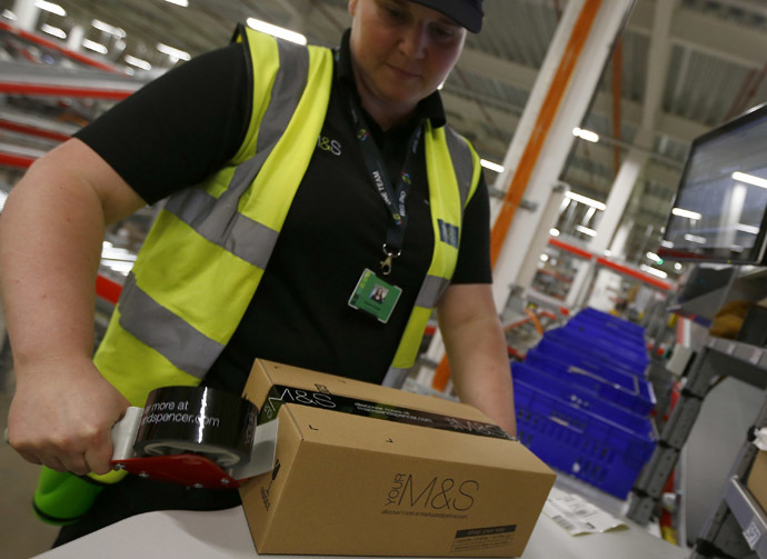 A worker boxes goods at the new Marks & Spencer e-commerce distribution centre in Castle Donington, central England May 8, 2013. (Reuters/Darren Staples)