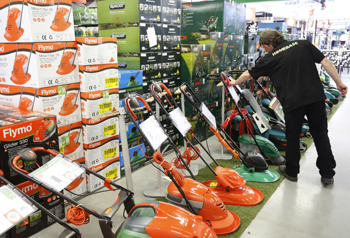 A sales assistant works on a display of lawnmowers at a Homebase store in Aylesford, South East England. (Reuters/Luke MacGregor)